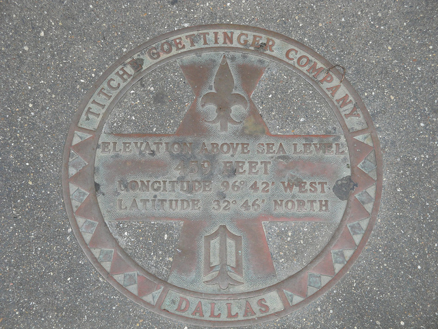 Marker in sidewalk pavement