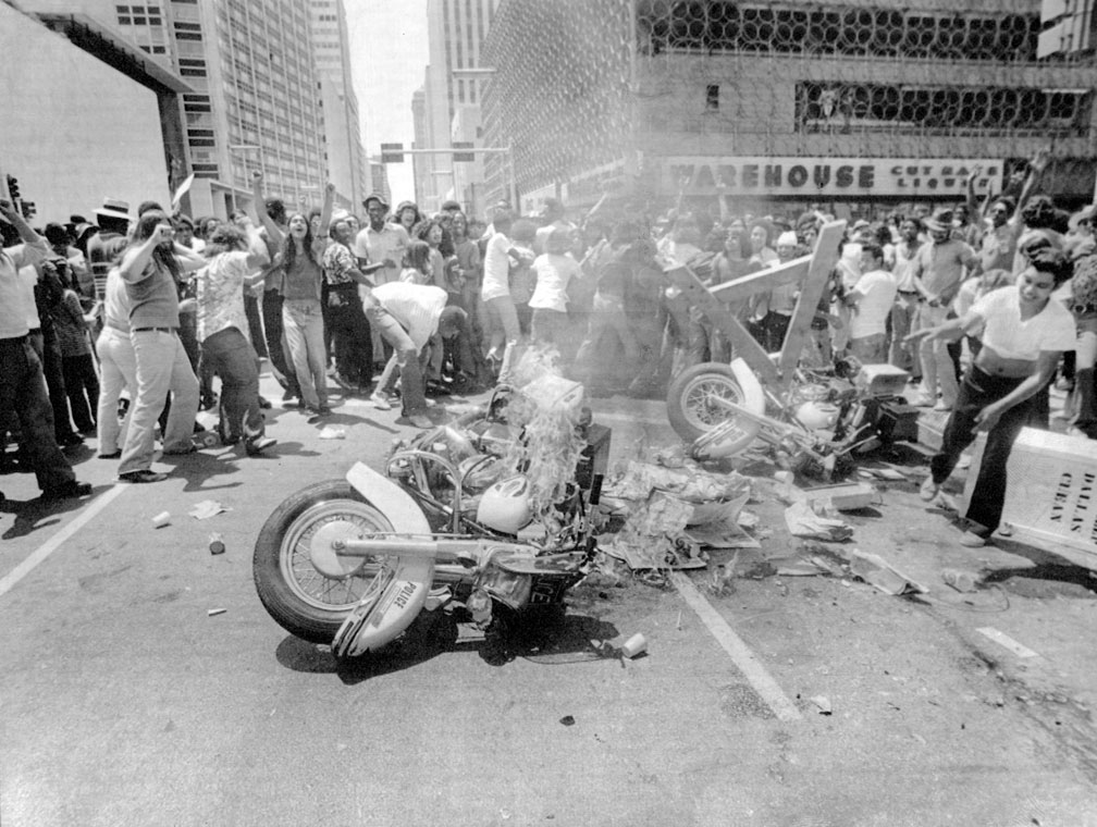 Rioters in street with burning police motorcycles
